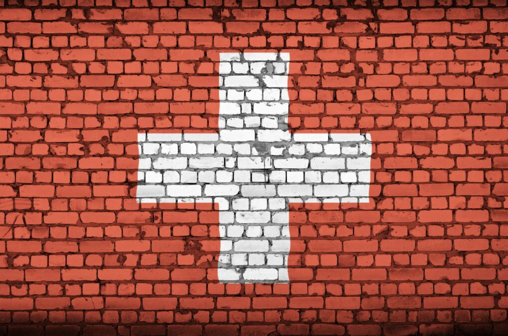 Switzerland flag is painted onto an old brick wall